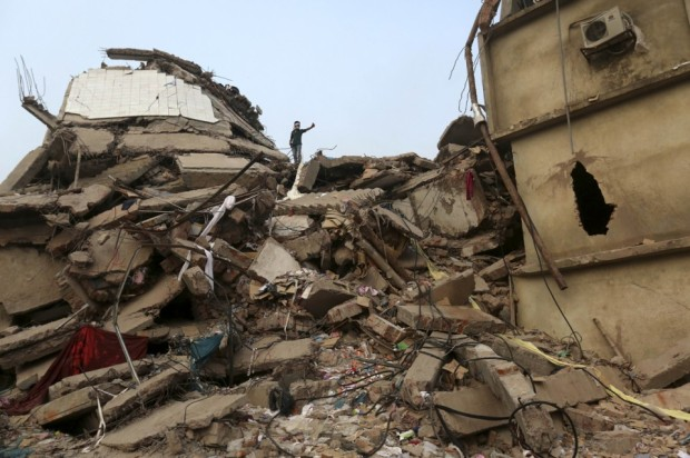 A-Bangladeshi-rescue-worker-walks-on-the-rubble-of-the-building-that-collapsed-Wednesday-in-Savar-on-April-27-2013.-AP-PhotoKevin-Frayer-960x639